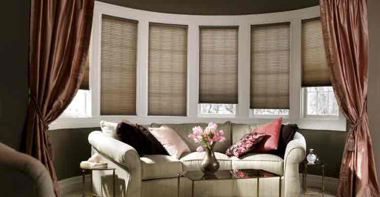 Vertical cellular shades in lounge bow window.