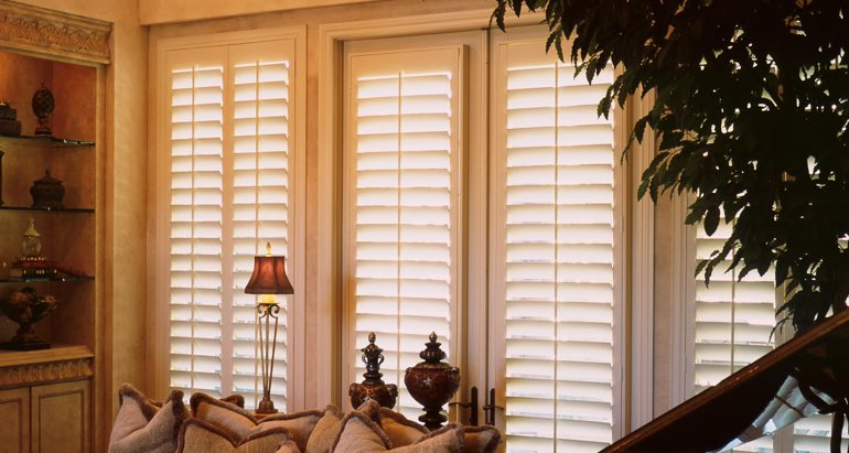Plantation shutters on french door and window in Chicago parlor