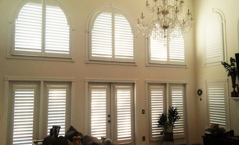 Television room in open concept Chicago home with plantation shutters on tall windows.