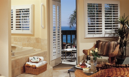 Plantation shutters on casement windows in a tropical room.