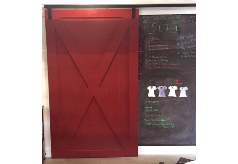 Red x-frame sliding barn door with black hardware next to chalkboard