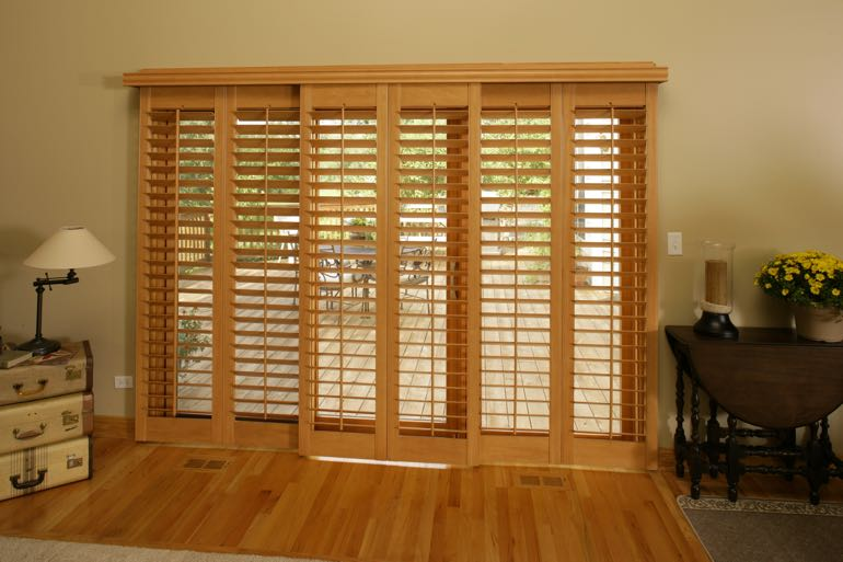 Wood shutters on sliding door going to outdoor porch.