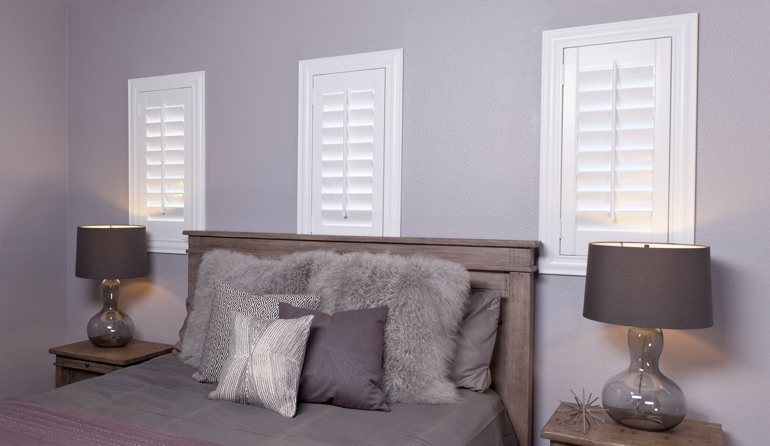 White plantation shutters in Chicago bedroom windows.