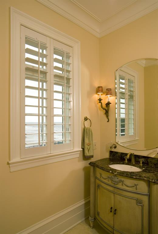 Plantation shutters in a bathroom looking out over ocean