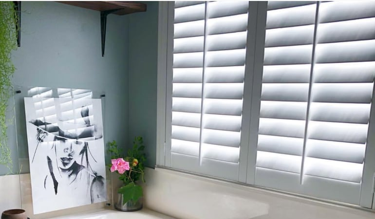 Plantation shutters over a bathroom window.