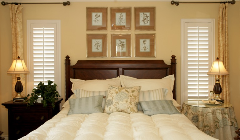 Tall plantation shutters framing bed in a bedroom in Chicago
