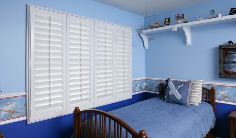 Large plantation shutters covering window in blue kids bedroom in Chicago